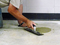 Repairing the cored holes in the concrete slab floor with fresh concrete and cleaning up the Vineland home.