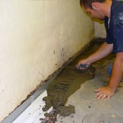 A basement waterproofer installing a perimeter drain system in Philadelphia