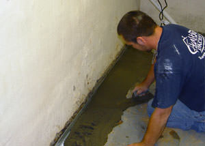 Restoring a concrete slab floor with fresh concrete after jackhammering it and installing a drain system in Wilmington.
